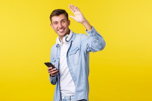 Рекламная концепция досуга, технологий и приложений. дружелюбный красивый счастливый человек проходит мимо друга, машет рукой, чтобы поздороваться, приветствуя человека, используя мобильный телефон и наушники.