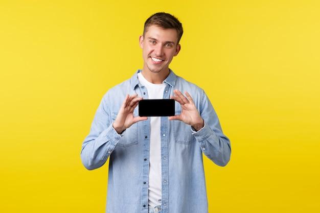 Рекламная концепция досуга, технологий и приложений. красивый улыбающийся белокурый мужчина, держащий смартфон обеими руками, представляет новую игру или мобильное приложение, показывая экран с довольным выражением лица.