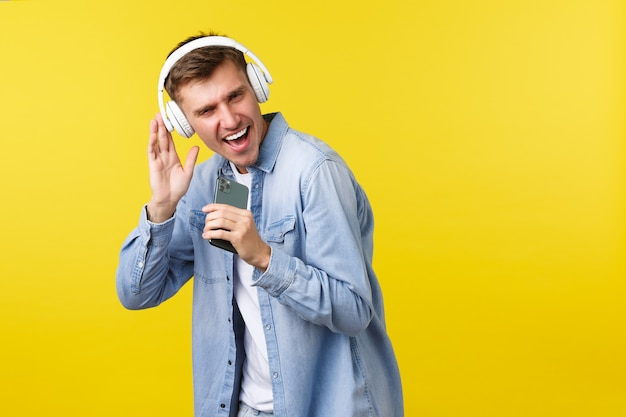 Рекламная концепция досуга, технологий и приложений. красивый молодой кавказский человек веселится, играет в караоке-приложении на мобильном телефоне, использует смартфон в качестве микрофона и поет в наушниках.