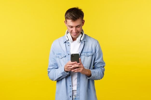 Рекламная концепция технологий и приложений для отдыха красивый молодой парень, студент, использующий мобильное фото ...
