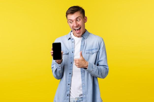 Рекламная концепция досуга, технологий и приложений. счастливый возбужденный блондин показывает большие пальцы руки, глядя и указывая на дисплей мобильного телефона, проверяя новое крутое промо или приложение.