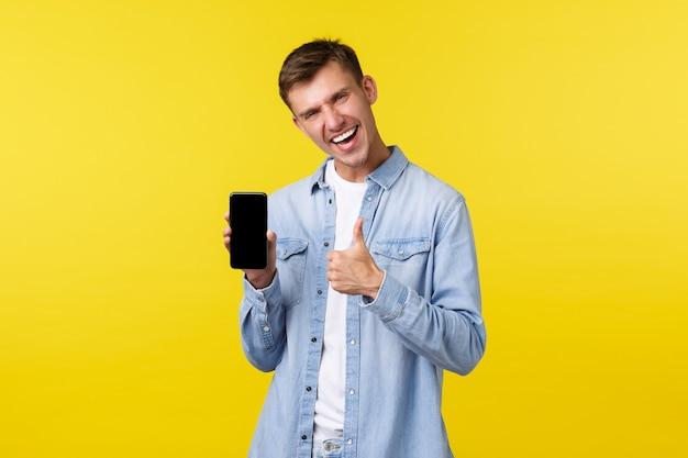 Рекламная концепция досуга, технологий и приложений. радостный восторженный красивый парень показывает палец вверх, как рекомендует приложение для мобильного телефона, показывает дисплей смартфона и улыбается.