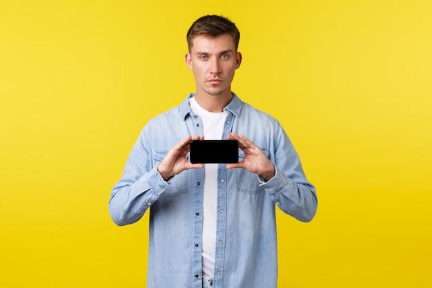 Рекламная концепция досуга, технологий и приложений. серьезный блондин пытается обратить внимание на важную информацию, показывая баннер или приложение на экране смартфона.
