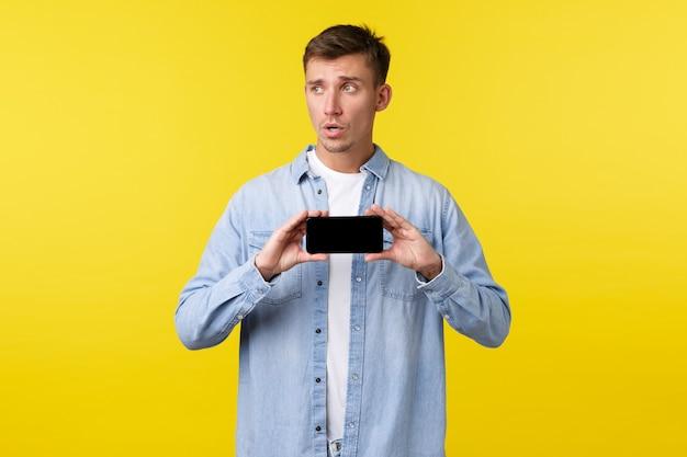 Рекламная концепция досуга, технологий и приложений. обеспокоенный нерешительный парень смотрит в сторону, нервно показывая что-то на экране смартфона, чувствуя себя неловко, желтый фон.