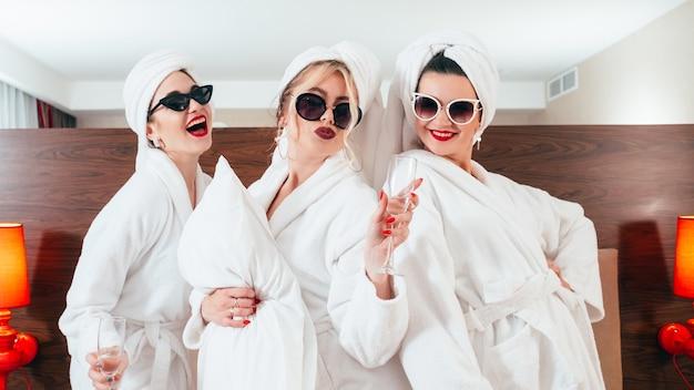 スパでの余暇。 bffの楽しさとリラクゼーション。シャンパンで笑顔の女性。サングラス、バスローブ、タオルターバン。