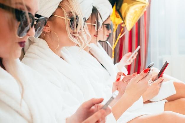 スパでの余暇。女性のリラクゼーションタイム。サングラスとバスローブのbffの列。手にスマートフォン。