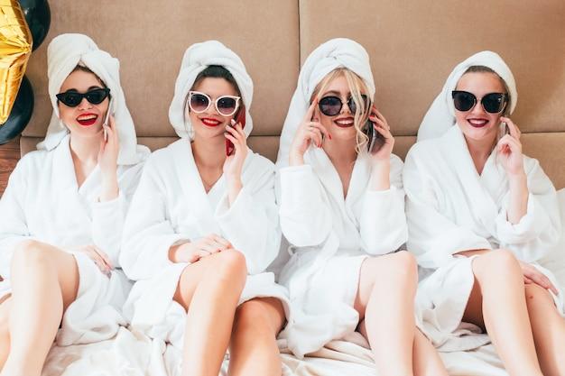 スパでの余暇。女性のリラクゼーションタイム。スマートフォンで話しているサングラスとバスローブのbffの列