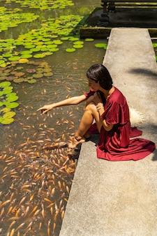 여가 시간. 물고기와 놀고 따뜻한 날씨를 즐기는 동안 지원에 앉아 귀여운 젊은 여성