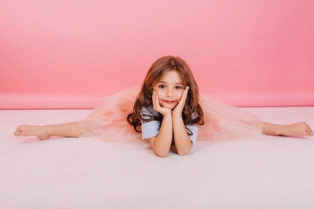 Leisure time of joyful charming little girl making gymnastics split on floor on pink background. elastic cute child in tulle skirt  with long brunette hair smiling to camera, expressing cheerful mood