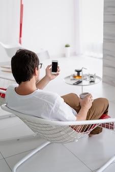 余暇。ティーカップと電話を保持しているテレビを見ている椅子に座っている白いシャツの男