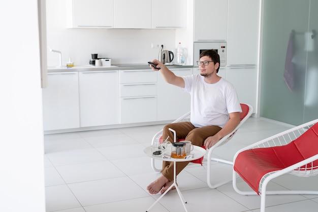 余暇。リモコンを持ってテレビを見ながら椅子に座っている男