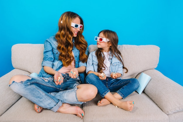 파란색 배경에 고립 된 소파에 그녀의 어린 딸과 함께 놀라운 아름 다운 어머니의 여가 시간. 3d 안경으로 영화보기, 팝콘 먹기, 서로 웃고