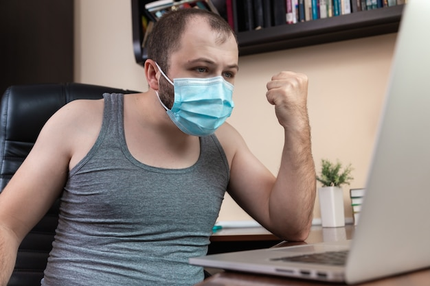 Leisure using laptop. a young bearded guy with face mask in home clothes uses laptop