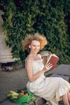余暇。手に本を持って階段に座っている若い女性