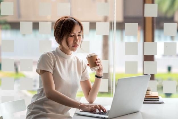 현대적인 사무실에서 커피를 마시고 노트북을 사용하는 아름다운 아시아 여성을 위해 일하는 여유로운 하루.