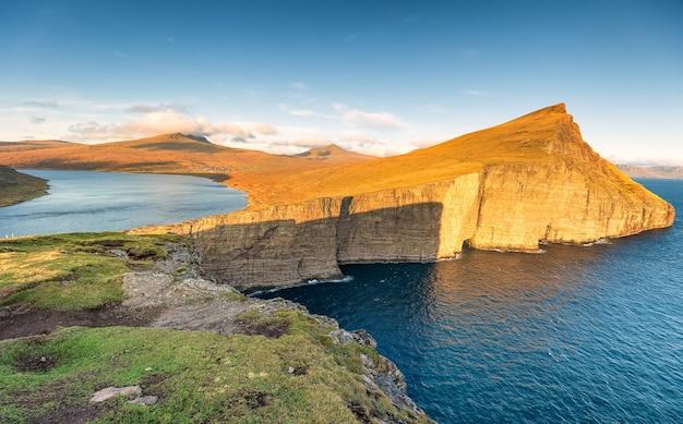 Озеро лейтисватн и атлантический океан на закате. остров вагар, фарерские острова. дания