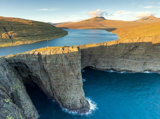 Озеро лейтисватн и траланипан, скала на закате. остров вагар, фарерские острова. дания
