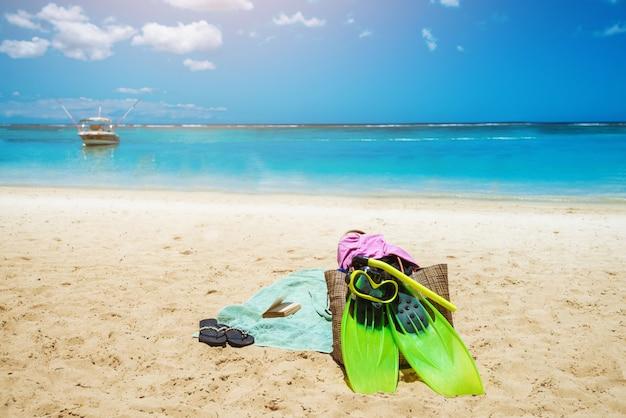 夏時間。ビーチビュー。砂の上のダイビングマスクとパドルlelft