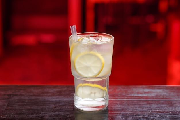 木製の大理石の表面にレモンアルコールカクテル。さわやかなレモンとジンのアルコールカクテルと木製のクーナーバーの氷。