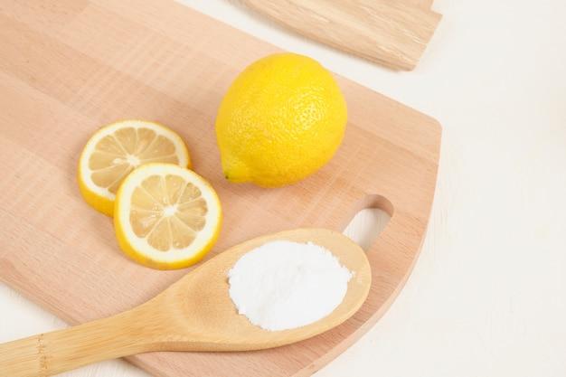 Лимон и пищевая сода на деревянной ложке, вязальная доска на бежевом фоне копией пространства