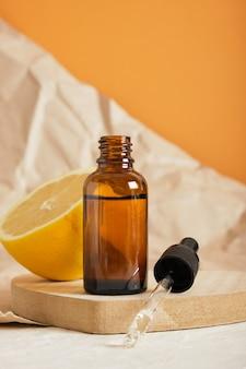 Лимонно-коричневая стеклянная бутылка с капельницей для сыворотки или косметического масла на деревянном подиуме в форме сердца, экологически чистая концепция ухода за телом