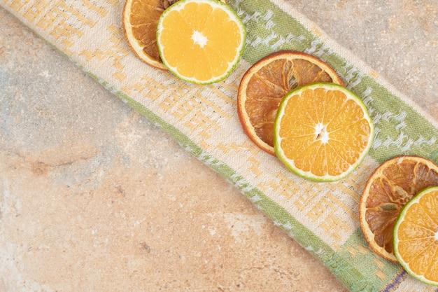 Лимон и сушеные апельсиновые дольки на скатерти.