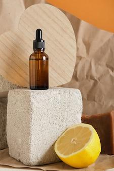 Лимонная и стеклянная коричневая бутылка сыворотки с пипеткой для ухода за кожей на бетонном подиуме концепция здоровья и красоты