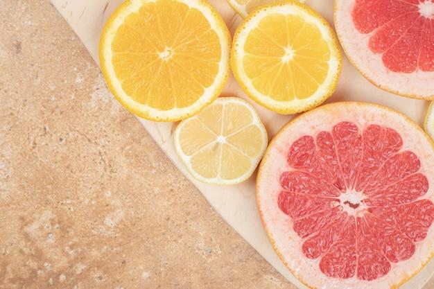 大理石の表面にレモンとグレープフルーツのスライス。