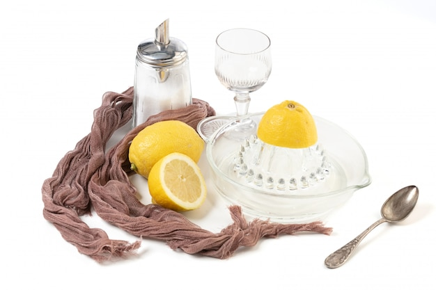 白い背景の上のガラスのレモンとレモンの絞り器