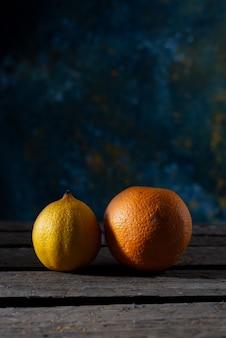 Лимон и апельсин на деревянном столе в деревенском стиле