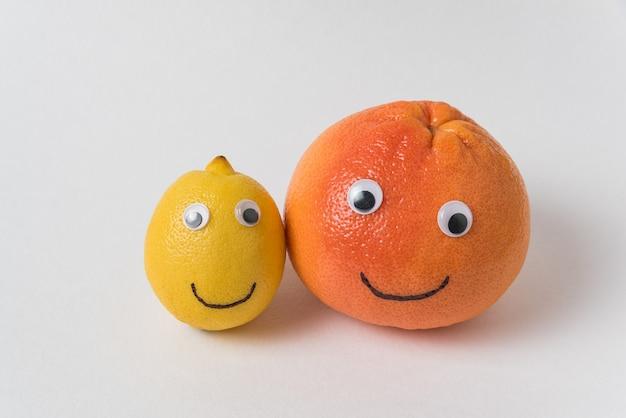 레몬과 오렌지 흰색 배경에 재미 있은 웃는 얼굴로. 개념은 다른 것과 다릅니다.