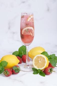 레몬과 딸기 레모네이드 민트 신선한 수제 유리, 여름 차가운 칵테일, 딸기 레몬 라임 모히토, 밝은 배경, 복사 공간, 상쾌한 여름 음료 개념.