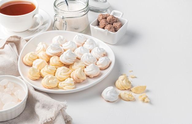 Лимонно-белые безе на фоне чашки чая и тростникового сахара. вид сбоку с копией пространства.