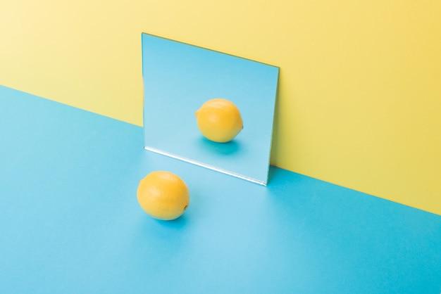 Lemon on blue table isolated on yellow near mirror