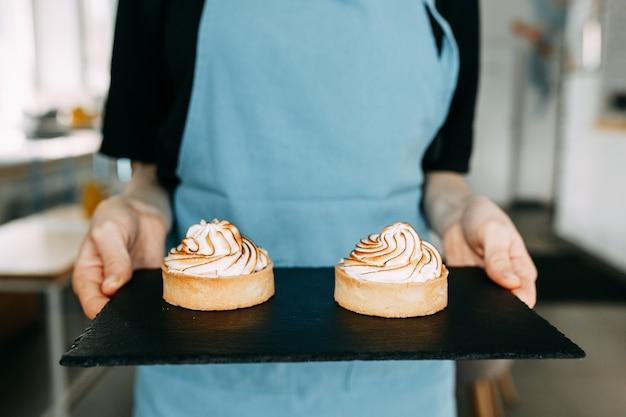 風通しの良いホイップクリームとレモンケーキ。デザートとウェイターの手でショートクラストペストリー。