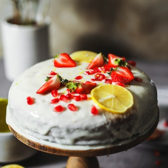 Lemon cake with fresh strawberries and pomegranate seeds