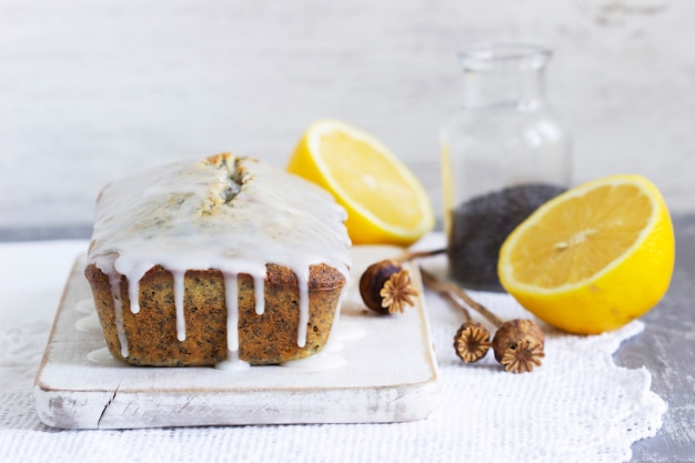 Lemon cake with poppy seeds, covered with glaze on a light background. selective focus.