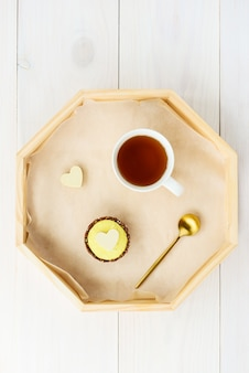 Lemon cashew cake with white chocolate heart and a cup of tea on a wooden tray.