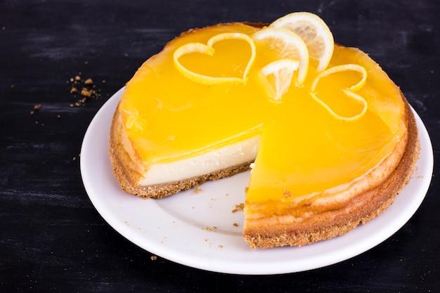 Lemon cheesecake on black background decorated with lemon zest close up