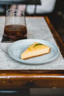 테이블에 아이스 커피와 레몬 치즈 케이크