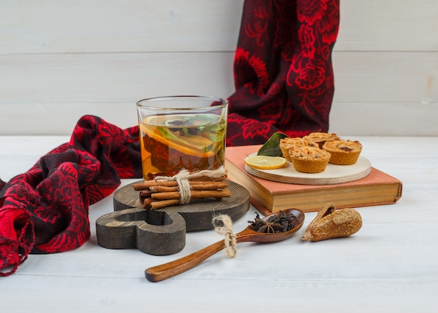 Lemon, chocolate chip cookies in plate with red scarf, white cookies, cinnamon, cloves and a book on white surface