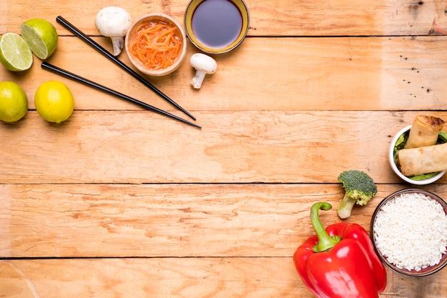 Lemon; chopsticks; mushroom; sauces; bell peppers; broccoli; rice and spring rolls on wooden plank