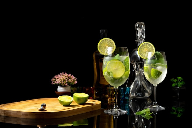 반사 검은색 배경 진과 레몬이 든 토닉 음료에 있는 유리 잔에 레몬 칵테일