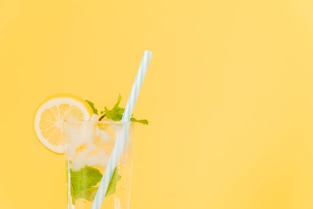 Lemon cocktail with plastic straw on yellow background