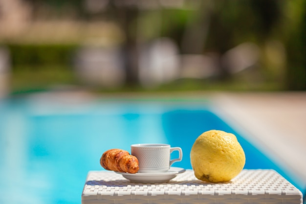 Lemon, coffee and croissant by the pool