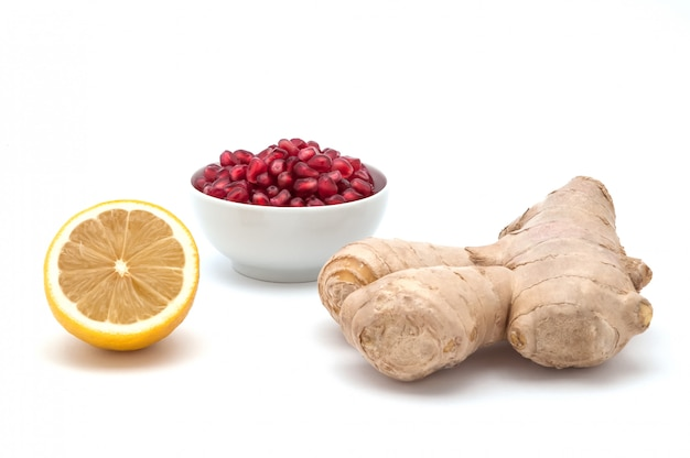 Lemon, a cup of pomegranate seeds and ginger on a white background. view from above.