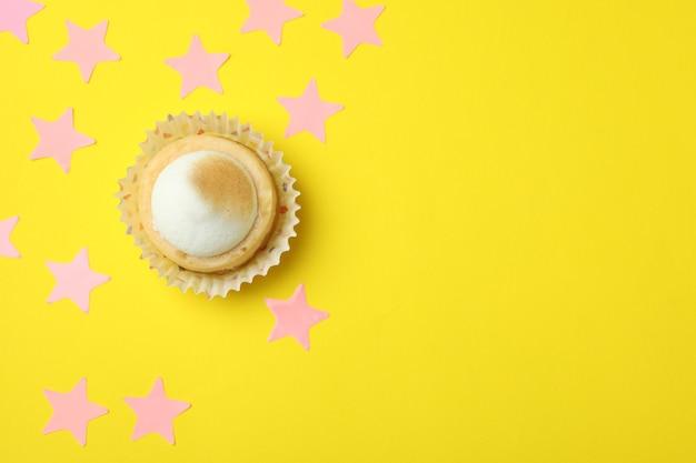 Лимонный кекс и розовые звезды на желтом фоне