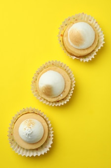 Lemon cupcakes on yellow background, top view