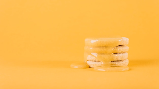 Lemon curd dripping over stack of cookies on yellow background