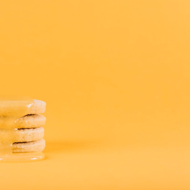Lemon curd dripping over stack of fresh cookies on yellow surface